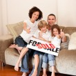 Foto Stock: Happy family sitting on a sofa