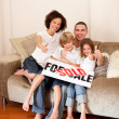 Stock Photo: Happy family sitting on a sofa