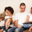 Charming family sitting on a sofa — Stock Photo