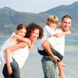 Parents giving two young children piggyback rides — Stock Photo