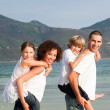 Happy family playing on the beach — Stock Photo