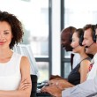 Attractive businesswoman with folded arms in a call center — Stockfoto