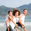 Couple giving children piggyback rides on the beach — Stock Photo