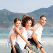 Stock Photo: Couple giving children piggyback rides on the beach