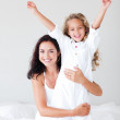Young Mother and daugther embracing on bed — Stock Photo