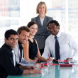 Stock Photo: Business team smiling at camerin office