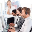 Concentrated female leader with a team on a call center - Stock Photo