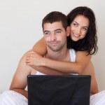 vrolijke paar met behulp van een laptop zittend op een bed — Stockfoto