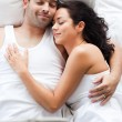 Radiant couple lying on a bed — Stockfoto