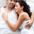 Foto Stock: Radiant couple lying on a bed