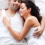 stralend koppel, liggend op een bed — Stockfoto