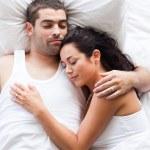 strålande par liggande på en säng — Stockfoto