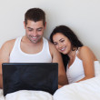 Cheerful couple using a laptop sitting on a bed — 图库照片