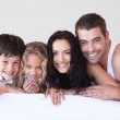 Happy family lying on their bed — Stock Photo