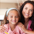 Happy mother helping her daughter for homework — Stock Photo