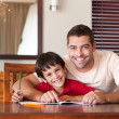 Confident father helping his son for homework — Stock Photo #10311626