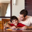 Royalty-Free Stock Photo: Confident father helping his son for homework