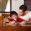 Confident father helping his son for homework — Stock Photo