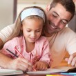 Cheerful father helping her daughter for homework - Stockfoto