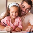 Cheerful father helping her daughter for homework — Stock Photo