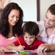 Radiant couple helping his son for homework — Stock Photo #10311659