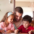 Smiling father helping his children for homework — Stock Photo #10311671