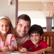 Smiling father helping his children for homework — Stock Photo #10311672