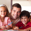 Stock Photo: Smiling father helping his children for homework