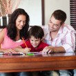 Radiant couple helping his son for homework — Stock Photo #10311677
