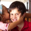 Cute girl kissing her brother — Stock Photo