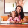 Cheerful mother helping her daughter for homework — Stock Photo