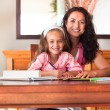 Cheerful mother helping her daughter for homework — Foto de Stock