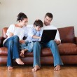 Parents and son playing with a laptop - Stockfoto