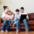 Happy family playing together with a laptop - Stockfoto