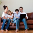 Family playing together with a laptop - Stockfoto