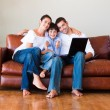 Happy family using a laptop with thumbs up — Stock Photo