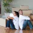 Lovely couple with unpacking boxes moving to a new house — Stock Photo