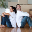 Lovely couple with unpacking boxes moving to a new house — Stock Photo #10311775