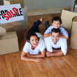 Family moving house on floor smiling at the camera — Foto Stock