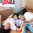 Smiling family in their new house lying on floor — Stock Photo #10311786