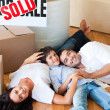 Parents and son moving house lying on floor - Foto de Stock  
