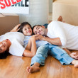 Family in a new house lying on floor with boxes — Stock Photo