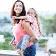 Mother giving daughter piggyback ride — Stock Photo #10311795