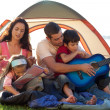 Happy family playing a guitar in a tent — Stock Photo