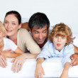 Stock Photo: Happy family together on bed