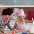 Lovely mother and her daughter baking in a kitchen — Stock Photo #10311927