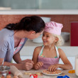 Stock Photo: Lovely mother and her daughter baking in a kitchen