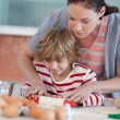 Nice mother and his son baking in a kitchen — Stock Photo