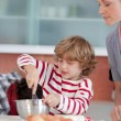Smiling mother baking at ome with her son — Stock Photo #10311970