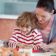 Smiling mother baking at ome with her son — Stock Photo